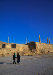 Two iranian women passing in front of the site of persepolis, Fars province, Marvdasht, Iran (Eric Lafforgue) Tags: 2people achaemenid adultsonly ancientcivilisation archaeology architectural architecture blue chador clearsky colorimage copyspace culture day desert heritage historical history iran iranianculture marvdasht middleeast monument onlywomen orient outdoors persepolis persia photography ruins shiraz sunny takhtejamshid travel traveldestinations twopeople unescoworldheritagesite vertical women womenonly farsprovince ir