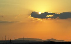 Sunset approaching over the wind turbines (Vee living life to the full) Tags: leger travel touring holiday nikond300 heathaze view road sky cloud sunset sunburst orange glow windmills turbines mountains fields