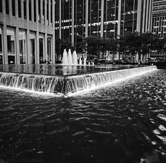 Fountain at Dusk - New York - Mamiya 6 - 50mm F/4 - HP5+ (divewizard) Tags: newyorkcity blackandwhite bw newyork building 120 6x6 blancoynegro film water fountain glass architecture analog mediumformat square 50mm lights blackwhite analgica noiretblanc manhattan rangefinder illuminated ilfordhp5 k2 hp5 lit mamiya6 weiss ilford f4 schwarz hp5plus pelcula newyorkcounty blackandwhitephotos 10020 schwarzundweiss ncps exxonbuilding 1251avenueoftheamericas chrisgrossman northcoastphotographicservices 229m g14f50mml built1986 725ft 54stories