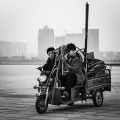 Coworkers (Go-tea 郭天) Tags: canon eos 100d street urban city china qingdao huangdao asia asian chinese people outside outdoor monochrome bw bnw black white blackwhite blackandwhithe men workers motobike motocycle loaded together pipe tools movement duty heavy tired sea side water building tall towers backside background space ride riding drive driving driver passenger motorcycle team colleague full hard difficult difficulty