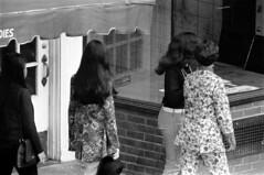 072868 15 (ndpa / s. lundeen, archivist) Tags: nick dewolf nickdewolf photographbynickdewolf blackwhite bw 1968 1960s 35mm july charlesstreet beaconhill candid people youngpeople pedestrians sidewalk boston massachusetts ma city citylife streetlife sliceoflife film monochrome blackandwhite building storefront clothes clothing fashion woman women youngwoman youngwomen purse handbag longhair brunette storewindow hat