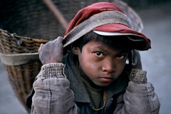 Forgotten Children by Penny Appeal (PennyAppeal.Org) Tags: 1998 himalayan trek young boy red hat carrying basket working child outdoors exterior portrait 0020913 marpha nepal annapurna region headstrap strap cap jacket porter outside carry