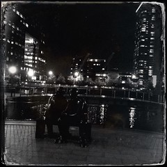 Two Men On A Bench (firstnameunknown) Tags: city sculpture london art water monochrome night reflections lights blackwhite cityscape publicart canarywharf twomenonabench gilespenny iphoneography hipstamatic lowylens dtypeplatefilm