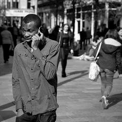 The Walk And Talk (Leanne Boulton) Tags: life lighting street city uk light shadow portrait people urban blackandwhite bw sunlight white man black detail male texture monochrome face mobile shirt youth contrast canon photography 50mm mono scotland living blackwhite focus shadows dof phone natural bright humanity bokeh outdoor expression glasgow candid young streetphotography scene communication human shade 7d conversation posture frown gesture tone facial chequered candidstreetphotography