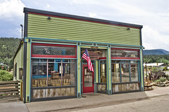 """Nederland's """"Crosscut"""" (brucetopher) Tags: crosscut hdr green mountain mountaintown town architecture victorian pseudo unfinished flag usflag reflection display store shop facade signage lonely old antique restoratino restore main street mainstreet downtown"""