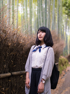 Young woman looking up in bamboo forest