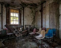 Overlooked. (Anonymous_Trespasser) Tags: windows abandoned rotting hospital chair nikon decay empty prison forgotten urbanexploration vacant peelingpaint decrepit filth asylum derelict psychiatric crumbling psychiatrichospital institution urbex kirkbride 20mmf28daf