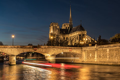 In the evening (Howard Ferrier) Tags: france cathedral waterway religiousbuildings longexposure dusk seine tourboat lighttrails transport paris river iledefrance night architecture bridge notredamecathedralparis europe iledelacite charterboat boat