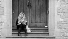 Studying (Just Ard) Tags: street door uk england people urban bw woman white black girl monochrome photography prime reading mono book nikon bath sitting candid streetphotography 85mm somerset doorway step sit nikkor unposed seated studying doorstep primelens d7000 justard