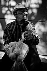 _DSC3628 (stimpsonjake) Tags: nikoncoolpixa 185mm streetphotography bucharest romania city candid blackandwhite bw monochrome oldman apples hat portrait beggar homeless