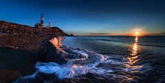 Over the horizon  (kaising_fung) Tags: lighthouse sunrise morning sea shore beach rocks waves