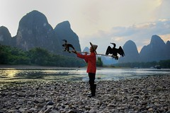 Life on the Li River, China. (najeebmahmud) Tags: nikon nikond810 nature nikkor2470mm nikkor d810 2470mm light landscape line rocks river reflections red mountains mountainside sky serene sunset clouds awesome asia china li yangshou wow white water bird birds couple people blur green yellow trees tree fishing