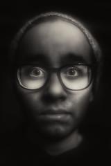 Curiosity (mckenziemedia) Tags: curious curiosity boy man blackandwhite monochrome glow lowkey portrait face glasses eyeglasses light shadows darkness night canon 5d markiii