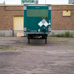 Green trailer parked behind building thumbnail