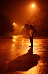 Rain depresses, rain refreshes. (karovaici) Tags: road street city trees light shadow portrait orange storm reflection wet water rain night clouds umbrella dark concrete streetlight warm moody foggy neighborhood receding slippery
