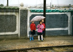 Watching at the track (Frühtau) Tags: dprk north korea people korean daily life children watching countryside nordkorea kids umbrella station bahnhof village rural area province asia asian east du nord leute town scene scenery 朝鲜 朝鮮 cháoxiān 地 outdoor корея северная كوريا الشمالية 北朝鮮 corea del norte corée coreia do coréia เกาหลีเหนือ βόρεια κορέα culture szene personen