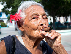 Old wrinkled woman with red flower smoking cigar (escape_travel) Tags: life old santiago portrait brown black flower senior face fashion lady female dark person healthy women adult habit time grandmother head cigarette smoke serbia cuba humor bad cancer lifestyle cigar retro human mature leisure years aged wisdom smoker relaxation cuban product addiction dependency tobacco santiagodecuba facial retirement unhealthy wrinkled lung