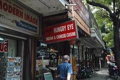 Hungry Eye - Sukhumvit Rd Bangkok (jcbkk1956) Tags: bangkok thailand street sukhumvit restaurant sign man walking hungry indian chinese eye streetfurniture nikon d70s nikkor 1870mmf3545 photoshop trees worldtrekker