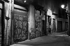 Carrer de la Palla (Gary Kinsman) Tags: barcelona old bw españa shop graffiti blackwhite spain alone quiet availablelight ambientlight grain medieval shutters noise desolate narrow gothicquarter alleys highiso lanes 2014 espanya barrigòtic canon50mmf14 elbarrigòtic carrerdelapalla canoneos5dmarkii canon5dmkii