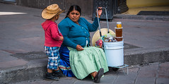 2016 - Mexico - San Luis Potosi - Bee Pollen & Honey Sales (Ted's photos - Returns late December) Tags: 2016 cropped mexico nikon nikond750 nikonfx sanluispotosi tedmcgrath tedsphotos tedsphotosmexico vignetting mother son strawhat pail bucket curb grate streetscene street people senora youngboy motherandson hoodie beepollen honey sweater apron sidewalk step sitting seated