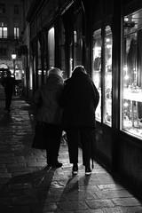 Night-Window-Shopping (PIXXELGAMES - Robert Krenker) Tags: newspaper news cafe kaffee vienna wien snapshot unknown candid portrait portret schwarzweiss blackandwhite blacknwhite bnw fujifilm fujinon filmsimulation lifestyle street streetstyle urban streetphotographer streetphotography biancoenero windowshopping ladies twoladies elderladies window shadow walk walking looking together frombehind