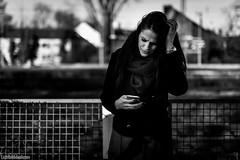 bad news (Lichtbildidealisten.) Tags: candid fence holiday cityscape white portrait art winter street city bw new blackandwhite woman cellphone railwaystation