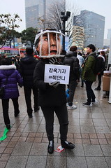 """Seoul Korea Kwanghwamun candle rally calling for President's ouster - """"Do Not Pass Go...Do Not Collect $200"""" (moreska) Tags: seoul korea kwanghwamun rally protest november26 democracy freespeech costume jail currentevents crowds caricatures signs hangul rainslick overcast afternoon highiso candid unstaged crosswalk rok asia"""
