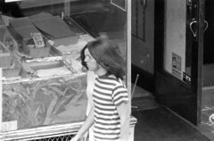 072868 10 (ndpa / s. lundeen, archivist) Tags: nick dewolf nickdewolf photographbynickdewolf blackwhite bw 1968 1960s 35mm july charlesstreet beaconhill candid people youngpeople pedestrians sidewalk boston massachusetts ma city citylife streetlife sliceoflife film monochrome blackandwhite building storefront clothes clothing fashion youngcouple man woman youngman youngwoman longhair stripedshirt door opendoor doorway storewindow store shop market fruit produce streetphotography windowdisplay sunday july28 window groceries stripes striped shirt carantenna