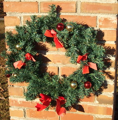 Wreath. (dccradio) Tags: lumberton nc northcarolina robesoncounty outdoors outside morning christmas decoration holiday ornament ribbon balls decorations ornaments red gold fadedribbon brick