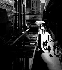 Binary People. Binary World. (Skuggzi) Tags: street city uk bridge shadow england urban blackandwhite bw woman sunlight man london love monochrome silhouette architecture modern contrast river holding couple europe noir unitedkingdom britain outdoor walk candid streetphotography romance h relationship gb scifi fujifilm docklands holdinghands sunlit futuristic technoir handholding companionship towerhamlets megacity