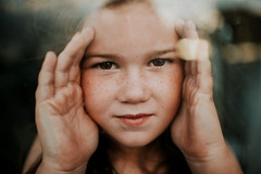 peek at you (demandaj) Tags: girl lxc nikon 35mm 14 window light reflection freckles child eyes