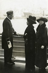 Emmeline and Christabel Pankhurst talking to an officer on board ship, c.1913-1914.