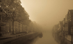 """Old"" Gorcum (marielledevalk) Tags: monochrome sepia river canal mist road port house city morning dutch holland boat"