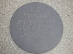 London St Pancras International Station - plaque - Imprisoned in a cage of sound (ell brown) Tags: eustonrd camden london greaterlondon england unitedkingdom greatbritain stpancras stpancrasstation stpancrasinternational londonstpancrasstation londonstpancrasinternationalstation eurostar kingscross midlandrd gradeilisted gradeilistedbuilding stpancrasstationandformermidlandgrandhotelcamden formermidlandgrandhotel railwayterminusandhotel trainshedterminusfacilitiesandoffices midlandgrandhotel georgegilbertscott williamhenrybarlow deepredgripperspatentnottinghambrickswithancasterstonedressings shaftsofgreyandredpeterheadgranite slatedroofs gothicrevivalbuilding terminusofthemidlandrailway euston kingscrossstpancras kingscrossstpancrasundergroundstation plaque imprisonedinacageofsoundeventhetrivialseemsprofound poem