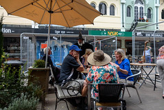Having a Chat (Jocey K) Tags: newzealand christchurch buildings city signs architecture people street newregentst cafes chairs tables clouds shops mural streetart painting artwork hats wizard