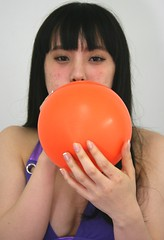 Creating Color Competition. (emotiroi auranaut) Tags: orange woman playing cute sexy beautiful beauty face lady female hair toy amusement hands pretty play purple feminine gorgeous air breath fingers seasonal balloon grow blowing blow entertainment inflatable round attractive mischievous lovely breathe mischief month playful bigger carefully breathing careful inflate femininity