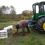 Students using a tractor to dig a hole.