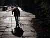 Silhouette (ThomasKrannich) Tags: street old city shadow urban silhouette germany walking person dresden alone hard highcontrast sigma olympus cobble sidewalk human walkway behind f28 crutch struggle 30mm pm2 elsasserstrase mtcand