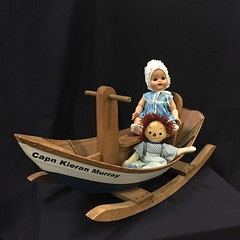 TOYS:  A rocking boat with antique dolls.