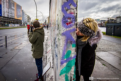 Around the Corner (photosbymcm) Tags: street travel winter streetart berlin cute art love wall germany graffiti couple europe gallery european artgallery peekaboo graf side eu east german berlinwall peek hiding eastside thewall eastsidegallery germans