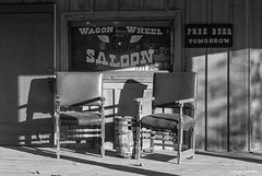 Outside the saloon (Photosuze) Tags: saloon pioneertown california desert chairs porch signs shadows table blackandwhite monochrome