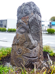 Rock Face(s) (Steve Taylor (Photography)) Tags: art sculpture carving blue brown green sad stone rock newzealand nz southisland canterbury christchurch cbd city plant curve face curl nose faces atlas debbietempletonpage lifeinvacantspaces