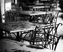 Rain Delay (Demmer S) Tags: outdoors dining tables chairs street streetphotography shootthestreet streetshots documentary urban city outside table chair iron metal wroughtiron castiron decorative patio furniture seating outdoor seats outdoorseating seat diningoutdoors outdoordining eatingoutside rain waterdrops raining raindrops water puddles dripping wet puddle bw monochrome blackwhite blackandwhite bnw blackwhitephotos blackwhitephoto