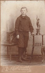 MY GREAT UNCLE MAX AS A BOY OF 10 IN 1906 (richie 59) Tags: inside oldphotograph olddays oldpicture oldphoto blackandwhite film photoscan filmcamera filmphotography person child boy greatuncle germany europe blackwhitepicture spandau table chair preteen 1906 1900s
