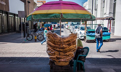 2016 - Mexico - San Luis Potosi - Pork Rind (Ted's photos - Returns late December) Tags: 2016 cropped mexico nikon nikond750 nikonfx sanluispotosi tedmcgrath tedsphotos tedsphotosmexico vignetting streetscene street people peopleandpaths umbrella porkrind streetsales bicycle shadow bollard