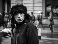 Cold and Bitter (Leanne Boulton) Tags: monochrome depthoffield people urban street candid portrait portraiture streetphotography candidstreetphotography candidportrait streetportrait streetlife eyecontact candideyecontact man male scar face facial expression look emotion feeling piercing glare stare harsh cold winter hat fur eyes intense stunning tone texture detail bokeh natural outdoor light shade shadow city scene human life living humanity society culture canon 7d 50mm black white blackwhite bw mono blackandwhite character glasgow scotland uk