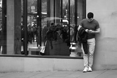 checking his phone by the phone shop (byronv2) Tags: edinburgh newtown edimbourg scotland blackandwhite blackwhite bw monochrome street candid peoplewatching princesstreet apple applestore man phone cellphone mobilephone