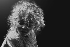 Angelic (Kapuschinsky) Tags: blackandwhite fineart fineartportrait portrait portraiture girl child curls hair hardlight sonyalpha sonya700 minolta dramatic emotive moody lookingdown sidelight naturallight face curly