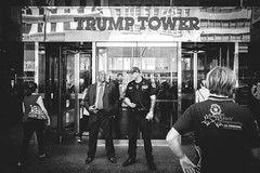 Guarding the President (L A Nolan) Tags: 185mmf28 18mm 28mmequiv day fujifilmx70 manhattan midtown newyork newyorkcity newyorknewyork ny nyc outdoors outside streetphotography thebigapple trumptower police cop suit blackman laughing