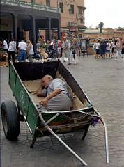 Man sleeping in Jemaa el-Fna (Loodoveeca) Tags: zenit122 35mm kodakcolorplus 200iso analog marrakech market marocco maroc morocco cart carretto sleeping nap